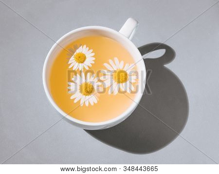 Herbal Tea With Fresh Chamomile Flowers. Cup Of Medicinal Chamomile Tea On A Gray Background. Top Vi