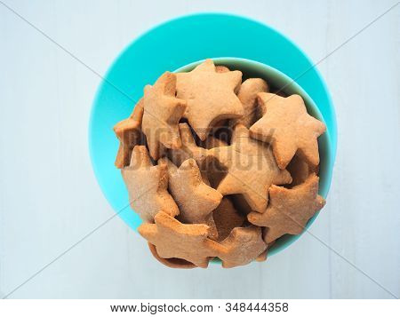 Star Shaped Ginger Cookies In A Turquoise Bowl On White Background