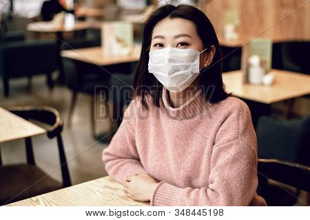 Asian Woman In A Protective Mask Is Sitting In A Cafe. Protecting The Population From Viruses By Pro