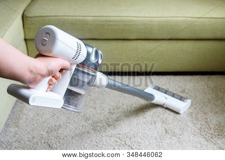 Wireless Vacuum Cleaner Used On Carpet In Room. Housework With New Upright Hoover. Person Holds Mode