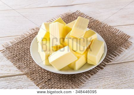 Rectangular Pieces Of Fresh Yellow Butter On A White Saucer Over A White Wooden Table. Dairy. Sandwi