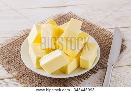Rectangular Pieces Of Fresh Yellow Butter On A White Saucer And Table Knife Over A White Wooden Tabl