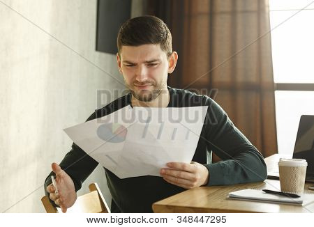 Discontented Office Worker Looking At Mistake In Documents Sitting In Modern Office, Selective Focus