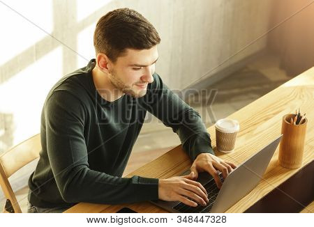Freelancer Copywriter Man Working At Laptop Computer Writing Article In Modern Office. High-angle Sh