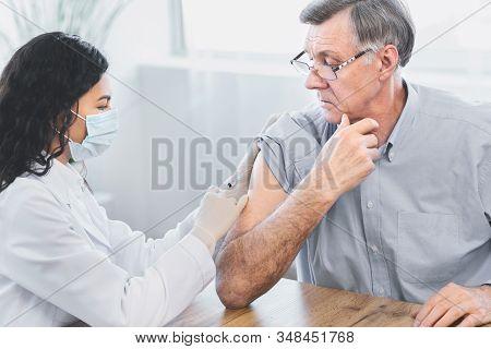 Seasonal Flu Shot. Brazilian Nurse In Medical Mask Injecting Tetanus Toxoid Vaccine To Senior Retire