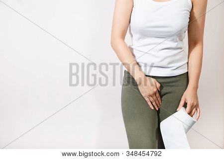 Woman Hand Holding Her Crotch Lower Abdomen And Tissue Or Toilet Paper Roll. Disorder, Diarrhea, Inc