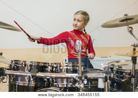 Teen Girl Playing The Drums. Teen Girls Are Having Fun Playing Drum Sets In Music Class. Girl In Red
