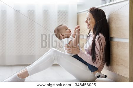 Family Fun. Cheerful Mom Tickling Her Toddler, Playing On Kitchen Floor, Free Space