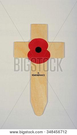 England, Uk - October 10, 2018 - A Single Red Poppy On A Small Wooden Cross Commemorating Remembranc