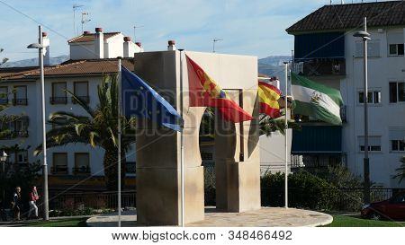 Alora, Spain - January 30, 2020: Flags Of Eu, Spain, Andalusia And Alora On Windy Day By Arabic Arch