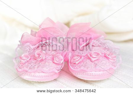 Pink Baby Booties From The Front, On White Crochet Blanket. Shoes With Lace, Shiny Ribbon And Silk R