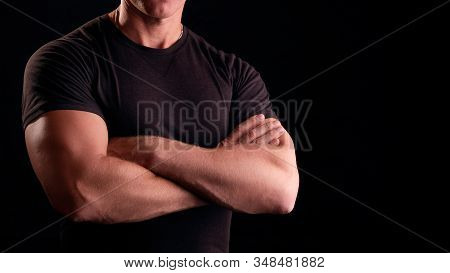 Strong Man On A Black Background. Concept Male Security Guard. A Man With Strong Arms. Male Security