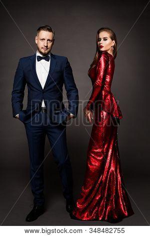 Luxury Couple, Beautiful Fashion Woman In Red Dress, Elegant Man In Suit Tuxedo, Studio Portrait