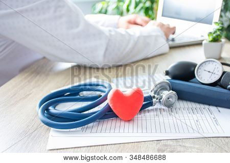 Doctor At Work On Laptop In Blurry Background, In Foreground - Shape Of Red Heart, Stethoscope,  Sph