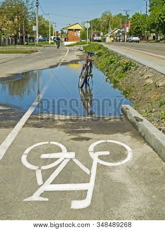 The Bike Drove Into A Large Puddle On The Bike Path.