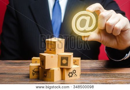 Businessman Holds An Email Internet Symbol Over Boxes. Sales Distribution Goods Products Online. Adv