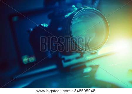 Modern Video Production Equipment. Telephoto Lens Closeup Photo. Dark Blue And Greenish Theme. Motio