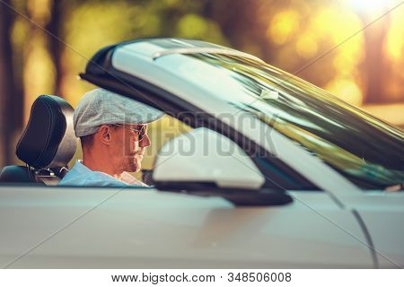 Young Retired Men Enjoying Summer Time Road Trip In His Convertible Car. Caucasian Men In His 30s Dr