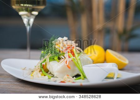 White Fish Seabass Fillet With Vegetables And White Wine On A Wooden Table In A Restaurant With Deco