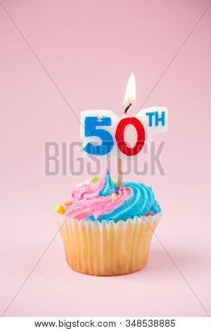 50th birthday cupcake with blue and pink icing on a pink background
