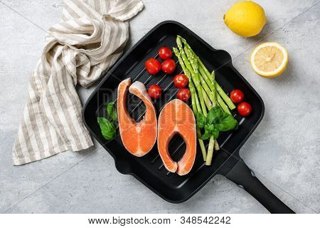 Salmon Steaks, Asparagus And Vegetables On A Grill Pan. Uncooked Fish Steak And Vegetables. Cooking