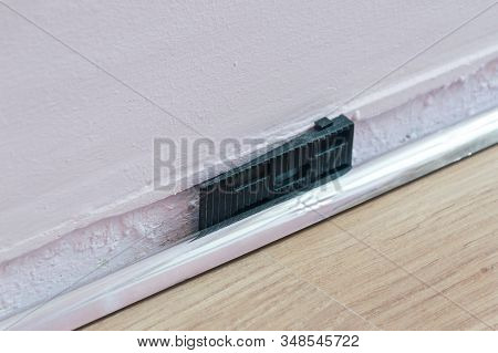 Black Dilation Wedge During Laying Laminate Flooring. Dilation Wedge Between Wall And Floor Panel.