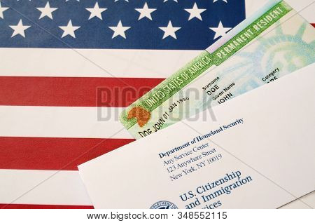 United States Permanent Resident Green Card From Dv-lottery Lies On United States Flag With Envelope