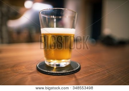 Half Full Pint Of Beer In Glass On Wooden Bar