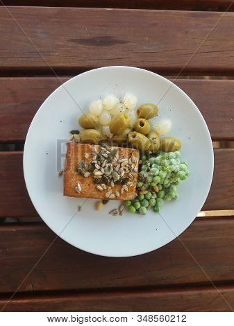 Tofu Based Dish With Green Olives, Pickled Onions And Frozen Peas