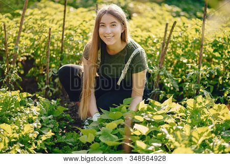 Beautiful Woman Works In A Garden Near The House