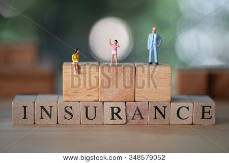 Miniature Family On Wood Block With Word Is Insurance. The Concept Of Insurance Of Family Life And P