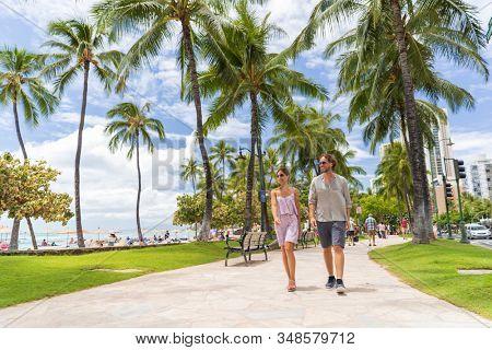 Honolulu city travel tourists couple walking on Waikiki beach boardwalk visiting Oahu island, USA summer travel holidays. Happy man and woman lifestyle.