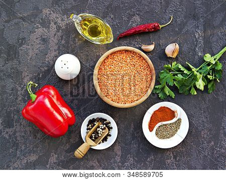 Ingredients For Cooking Lentil Hummus On A Dark Concrete Background: Red Lentils, Olive Oil, Sweet R