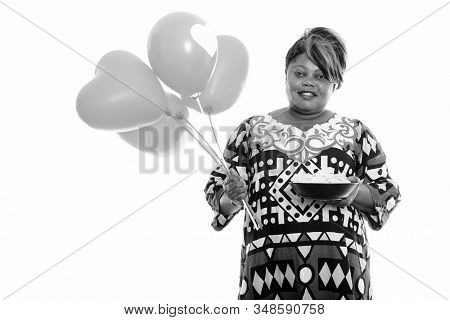 Happy Overweight African Woman Holding Bowl Of Potato Chips And Bunch Of Balloons