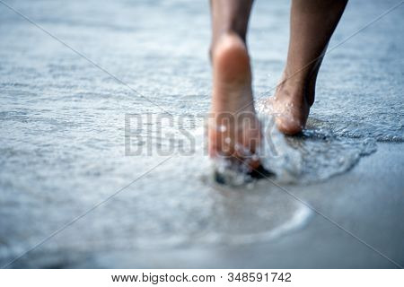 Woman Bare Foot Walking On The Summer Beach. Close Up Leg Of Young Woman Walking Along Wave Of Sea W