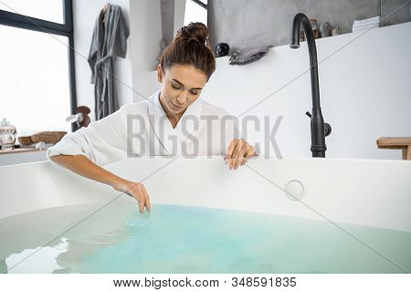 Beautiful Modern Girl Looking At The Bathwater