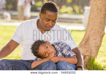 African American Father Worried About His Mixed Race Son as They Sit in the Park. poster