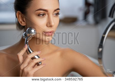 Girl Massaging Her Cheek With A Roller