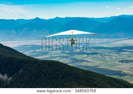 Man Flies With His Hang Gliding Over Rural Fields In Clear Sunny Day. Long Shot. Beautiful Kootenay