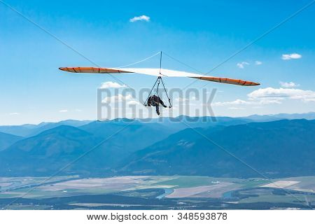 Hang Glider Man Flying In Clear Sunny Day. Flight Over Kootenay Valley Mountains, Creston, British C