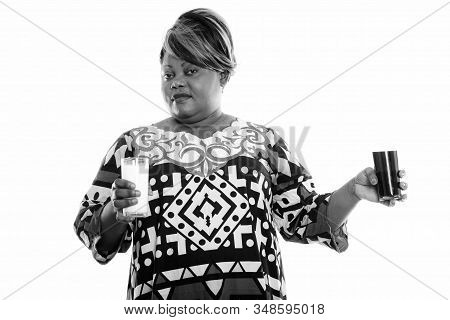 Overweight African Woman Choosing Between Glass Of Milk While Holding Glass Of Soda Drink