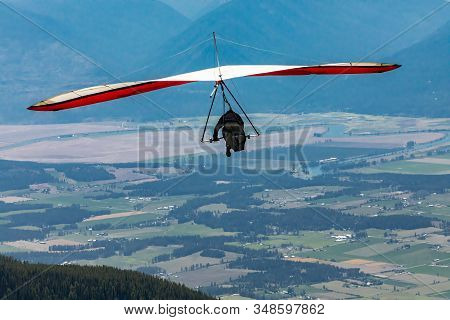 Hang Gliding In Action. Hang Glider Pilot Launching Over The Kootenay Valley Mountains, Creston, Bri