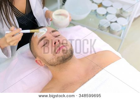 Cosmetologist Is Applying White Moisturizing Mask On Mans Face Using Brush In Beauty Clinic, Face Cl