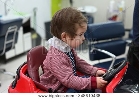 The Child Is Preparing For A Haircut. The First Haircut Of The Child At The Hairdresser. Baby Haircu
