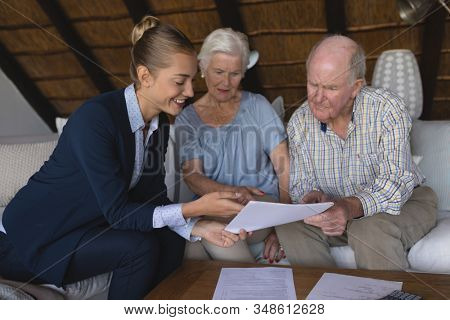 Front view of a female doctor and senior couple looking and discussing over medical reports they hold in their hands at home