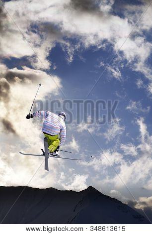 Freestyle Ski Jumper With Crossed Skis In Snowy Mountains And Blue Sky With Sunlit Clouds At Winter