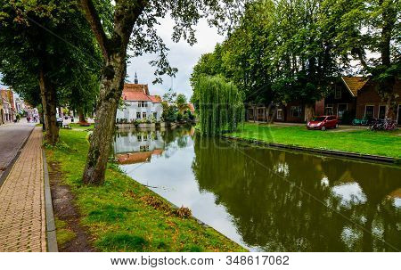 Edam, Netherlands, August 2019. One Of The Pretty Canals Of This City: The Foliage Of The Trees Is R
