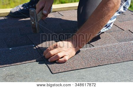 Roofer Contractor Laying Asphalt Shingles On House Rooftop. Roofer Nailing Asphalt Shingles On The H