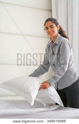 Maid Doing Room Service In Hotel, She Is Making Up The Beds. Maid Making Bed In Hotel Room. Housekee