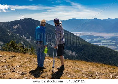 Two Friends Discussing Flight Plan On Hang Glider. A Beautiful Hilltop Landscape. Extremal Hikers Lo